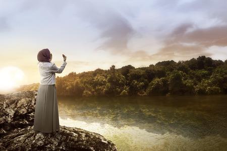 Junge muslimische Frau , die auf dem Felsen am See steht Standard-Bild - 58684743