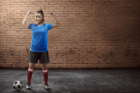 female soccer: Image of young female soccer player standing on the alley