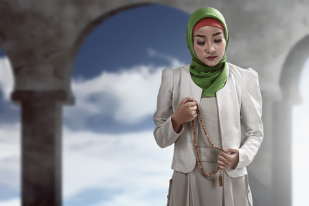 religious clothing: Image of muslim woman praying over mosque background