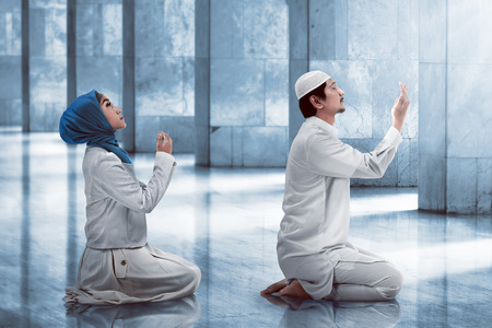 Young muslim couple praying inside the mosque Stock Photo