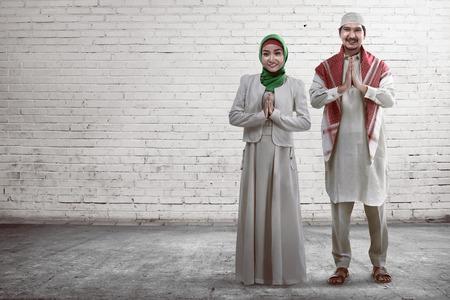 femmes muslim: Jeune couple musulman souriant avec brique mur blanc fond