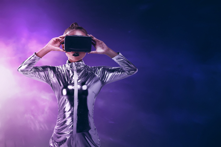 virtual world: Pretty asian woman wearing silver latex jumpsuit and VR headset inside virtual world. Virtual reality concept Stock Photo