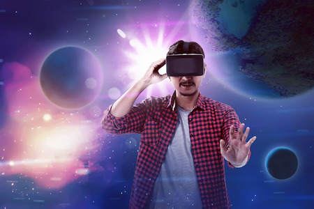 Young asian man wear VR headset get into virtual reality world. Virtual reality concept