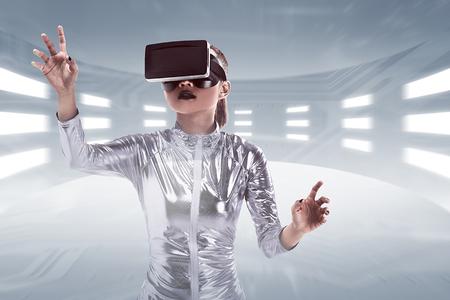 Jonge vrij Aziatische vrouw die VR-hoofdtelefoon binnen virtuele wereld draagt. Virtueel realiteitsconcept Stockfoto