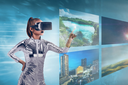 jumpsuit: Pretty asian woman wearing silver latex jumpsuit and VR headset inside virtual world. Virtual reality concept Stock Photo