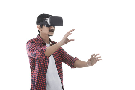 experiencing: Young asian man experiencing virtual reality through a VR headset isolated on white background
