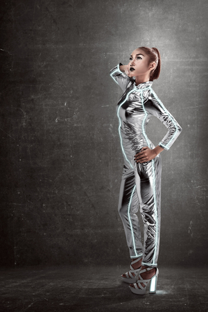 jumpsuit: Asian woman wearing latex jumpsuit posing over grunge background