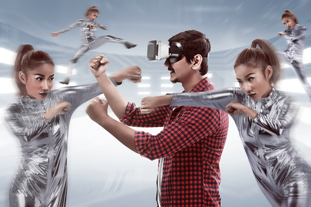 Young asian man using VR headset for playing fighting game Stock Photo