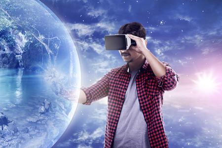 Joven asiático desgaste hombre dispositivo de realidad virtual entrar en el mundo de realidad virtual