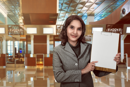 Customer service operator woman with headset smiling show empty paperboard. You can put your design on the board