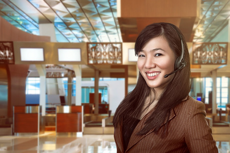 Customer service operator woman with headset smiling over airport background