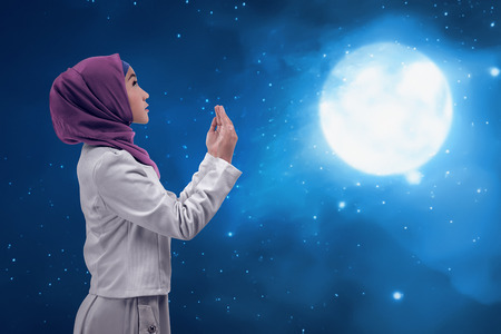 doa: Young asian muslim woman praying to god in the night, prayer with great wisdom. Under the moon
