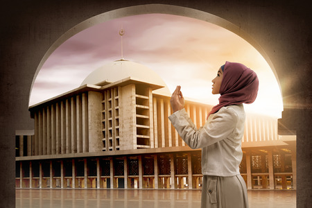 doa: Young asian woman praying to god with mosque background, she wearing hijab style