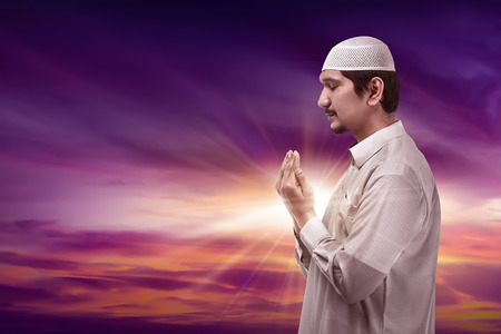 Young asian muslim man praying to god on silhouette background wearing cap Stock Photo