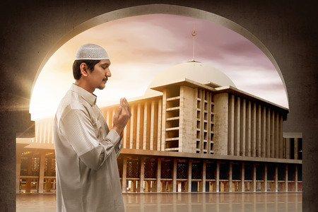 Young muslim asian man praying to god, muslim dress and wear caps with mosque background Stockfoto