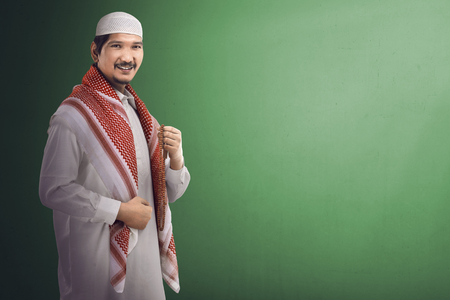 年轻的亚洲穆斯林男子穿着整洁的衣服,手里拿着念珠