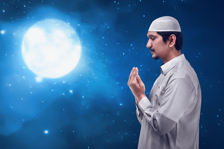Young asian muslim man praying to god in the night, prayer with great wisdom, he wearing cap. Under the moon