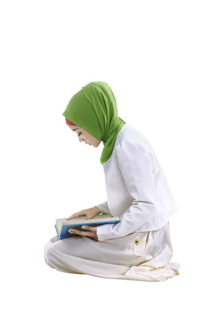 Young asian muslim woman reading the koran and shes concentrated reading, isolated background