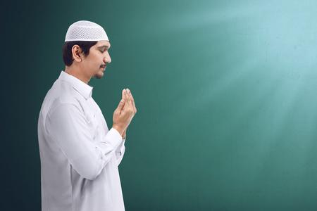Young asian muslim man praying to god, muslim dress and wear caps
