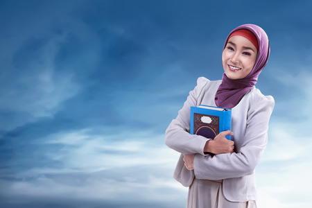 Young asian muslim woman wearing hijab and holding koran with blue sky backround Stock Photo