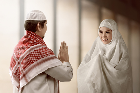 meet and greet: Asian muslim man and woman  greet each other with muslim tradition with mosque background.