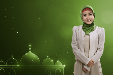 Young asian muslim woman give smile with green background template your giftcard
