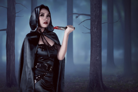 sexy black woman: Asian witch woman holding  bloodstained knife in forest with fog background Stock Photo