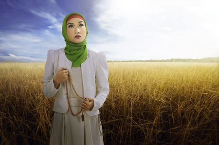 Young asian muslim woman look beauty with hijab style. holding the rosary and savana background