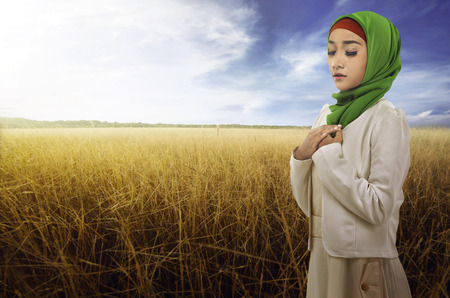Side of view young asian muslim woman wearing hijab with savana background Stock Photo
