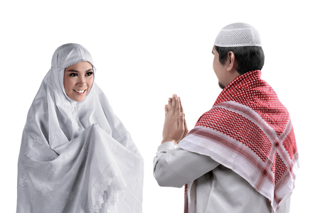 Asian muslim man and woman  greet each other with muslim tradition. isolated white background