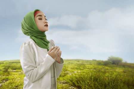 Side of view young asian muslim woman look beauty with hijab style. green meadow background