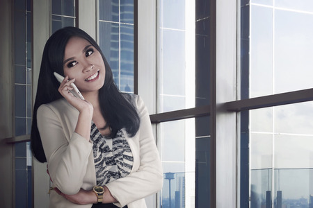 preety: Young and beauty asian business woman holding phone on office room with smile expression
