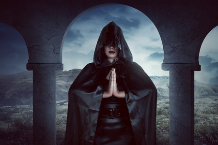 black magic: Young asian witch woman, her hand still spell magic, she wearing black costume in empty terrace