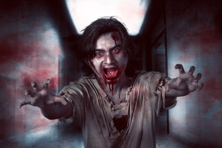 unkind: Asian zombie man in the empty room with angry expression and blood on his mouth