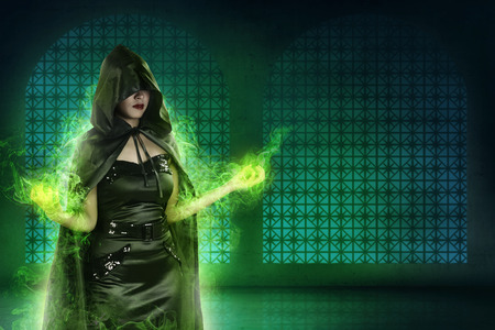 Asian witch woman wearing black costume in empty room. Her hand gesture out of green light magic