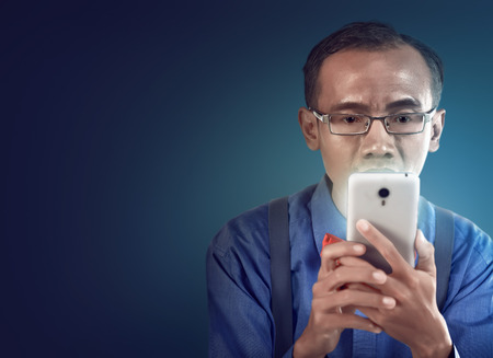 nerdy: Nerdy man holding cellphone and look concentration using it