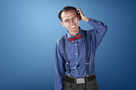 nerdy: Nerdy business man confused with blue background, dressed blue and bow tie with suspender