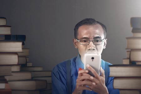 nerdy: Nerdy man with serious expression holding smartphone, in empty room with stacking books background