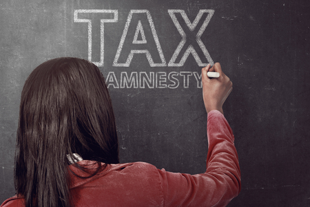 woman holding money: Business woman writing tax amnesty quotes on the black board with chalk Stock Photo