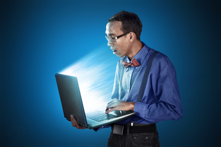nerdy: Nerdy man use laptop with standing position, gawk face and looks like stupid man Stock Photo