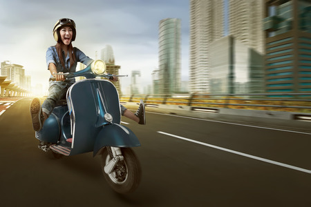 Asian woman riding scooter and wearing helmet on the street