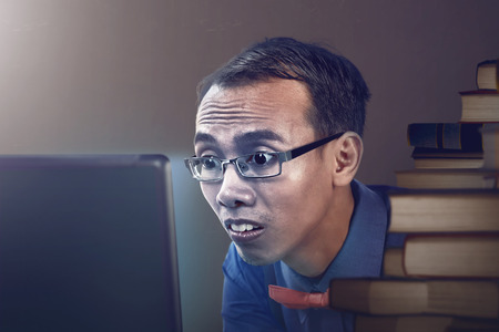 bulging eyes: Nerdy man studying with laptop, looks seriously and his eyes bulging up Stock Photo