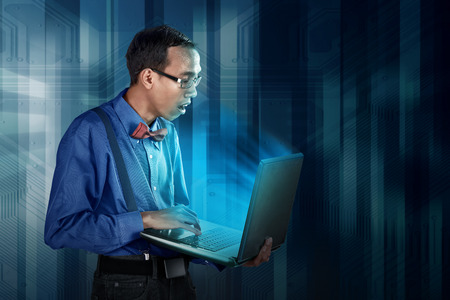 geeky: Nerdy man using laptop with gawk face expression, wearing formal shirt with bow and tie Stock Photo