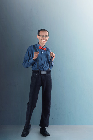 Nerdy man pose in the studio, wearing formal cloth, bow, tie, and suspender with smile expression