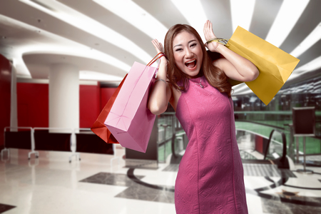 paperbag: Portrait of happy asian woman holding in her hands lot of shopping bag on inside mall background