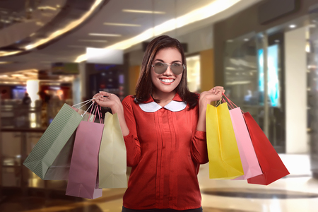 paperbag: Happy beautiful asian woman with shopping bags stands at shop Stock Photo