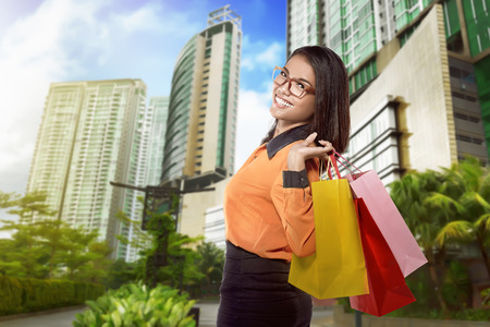 Young attractive asian woman walking on the streets with shopping bags Stock Photo