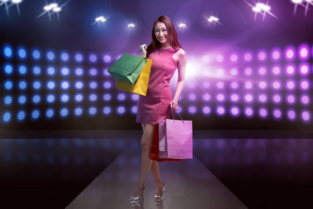 paperbag: Young happy smiling asian woman with shopping bags on the stage