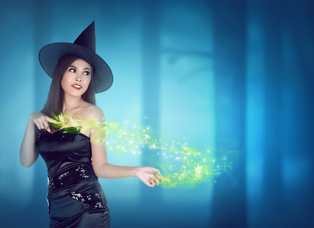 hands off: Asian witch woman with black hat and in her hands off light