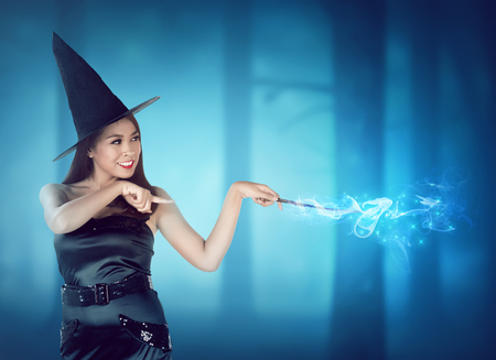 Beautiful young witch pointing and conjure something in the forest at midnight